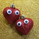Two hearts with eyes in the golden background glitter Stock Image