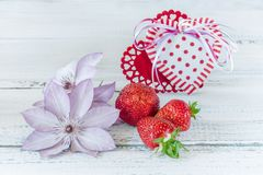 Two hearts from fabric with ripe strawberries in a pink ceramic Cup gift for Valentine`s Day on a blue wooden background with del royalty free stock photography