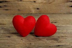Two hearts. Two felt textured hearts on weathered wood royalty free stock photography