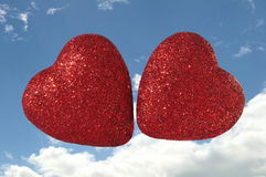 Two Hearts Floating in the AIr. Two Glittery Red Hearts Floating in Cloudy Blue Sky Stock Photo