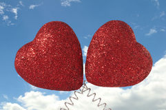Two Hearts. Two Glittery Red Hearts on Cloudy Blue Sky Background Stock Photos