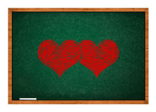 Two hearts on green chalkboard Stock Photos