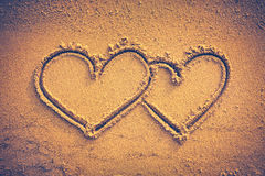 Two hearts handwritten on seashore sand. Vignette and vintage to Stock Images