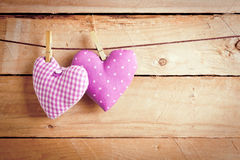 Two Hearts Hanging On Line. Two pretty pink material Valentine hearts hanging on a line with clothes pags over wooden boards Royalty Free Stock Photography