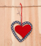 Two hearts hung up on the string. On wooden background Royalty Free Stock Photography