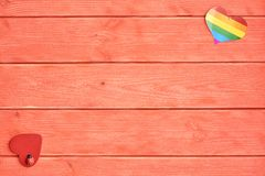 Two hearts lie on a wooden background color of living coral. One heart with a rainbow of LGBT community and the other red. Two hearts lie on a background the stock images