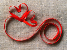 Two hearts and lock. Red valentine's ribbon on the canvas Stock Photography