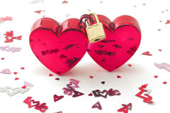 Two hearts locked, with small decorations. Two red hearts connected with padlock, with small decorations, on white background Royalty Free Stock Images