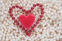 Two hearts lying on the white beads Royalty Free Stock Photography