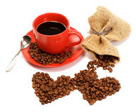 Two hearts made from coffee beans around a cup of coffee. Royalty Free Stock Images