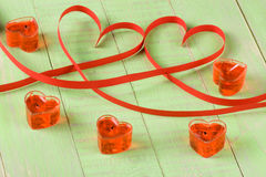 Two hearts made of red paper ribbon with candles isolated on white background Stock Photos