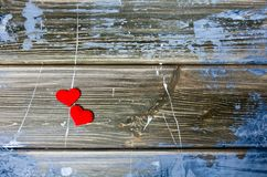 Two hearts in the middle of wooden background with blue and white paint royalty free stock images