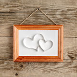 Two hearts in old picture frame Stock Image