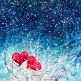 Two hearts over blue background with snowfall. Two valentine hearts on the white branch over dark blue frozen background with snow falling down Stock Photography