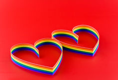 Two hearts,paint  of a colour gay flag in red. Royalty Free Stock Photos