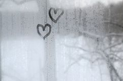 Two hearts painted on a misted glass in winter.  royalty free stock photos