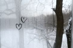 Two hearts painted on a misted glass in winter.  stock image