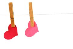 Two Hearts Pegged. Two hearts clipped with cloths pegs to a line stock photo