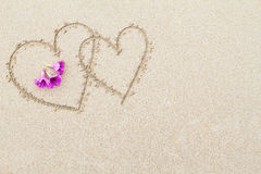 Two hearts with pink flowers on the beach surface background Stock Photo