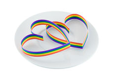 Two hearts on plate,paint of a colour gay flag. Single heart, paint of a six-colour gay flag on white plate. Isolated on white stock image