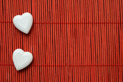 Two hearts on red bamboo lined Stock Images