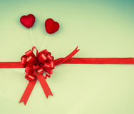 Two hearts and red bow with ribbon, love background Royalty Free Stock Images