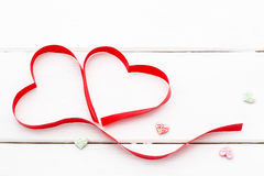 Two hearts of red ribbon and some small hearts on white wooden background Royalty Free Stock Photo