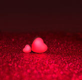 Two Hearts On Red Sparkle Glitter Background Stock Photo