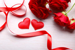 Two hearts, ribbon and red roses on table Royalty Free Stock Image