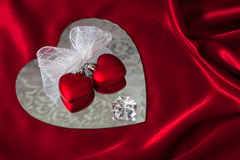 Two hearts ribbon tied with diamond sit on mirror (P) Stock Photography