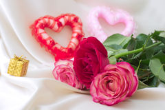 Two hearts and roses. On a silk background Royalty Free Stock Photography