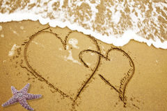 Two hearts on a sand Stock Photos