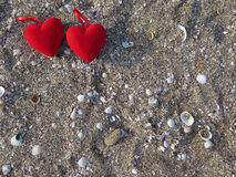 Two hearts on the sand with seashells. Stock Photo