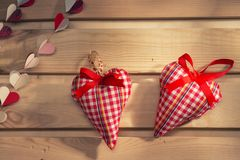 Two hearts sewn from red plaid fabric on the board, Stock Images