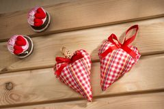 Two hearts sewn from red plaid fabric on the board. A symbol of love Stock Photography