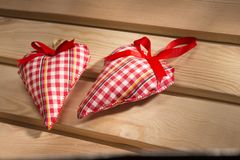 Two hearts sewn from red plaid fabric on the board Royalty Free Stock Image