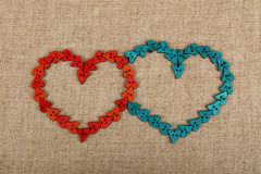 Two hearts shaped of sewing buttons on canvas. Two hearts together shaped of red and blue handmade wooden sewing buttons on linen canvas, elevated top view Royalty Free Stock Images