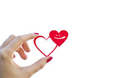 Two hearts and smile. Woman hand is holding the red shape of two hearts with a smile inside of one of them with an empty space on white royalty free stock photo