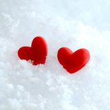 Two hearts in the snow. Studio macro of two red hearts lying in the snow. Copy space Royalty Free Stock Photography
