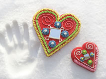 Two hearts in the snow. With a handprint Stock Photo