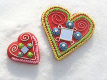 Two hearts in the snow. With a handprint Royalty Free Stock Photos