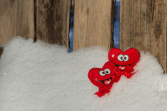 Two hearts  on the snow. Two smiling hearts  on the snow next to fence Stock Photos