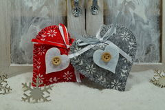 Two hearts on the snow under the window. The magic of Christmas Stock Photography
