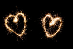 Two hearts of sparklers. On black background Stock Image