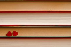 Two hearts on a stack of books close up. Two red hearts on a stack of books close up abstract background Royalty Free Stock Photography
