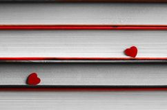 Two hearts on a stack of books close up. Two red hearts on a stack of books close up abstract background Stock Image