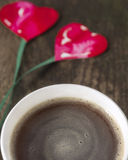 Two hearts on string, coffee cup on old wooden boards Stock Image