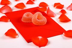 Two hearts from sugar candies on red envelope and petals Stock Photography