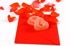 Two hearts from sugar candies on red envelope and petals Stock Images