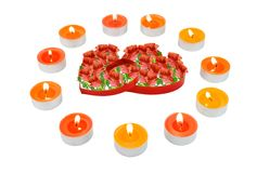 Two hearts, surrounded small candles. Stock Images